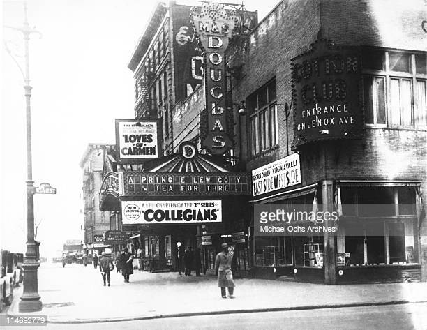 A view of the corner of Lennox Avenue and 147th Street in Harlem showing the exterior of the MS Douglas Theatre and a sign for the Cotton Club a few...