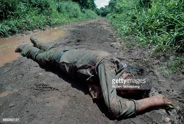 View of the corpse of an unidentified People's Revolutionary Army guerrilla on a muddy dirt road in San Miguel Province El Salvador September 1 1983...