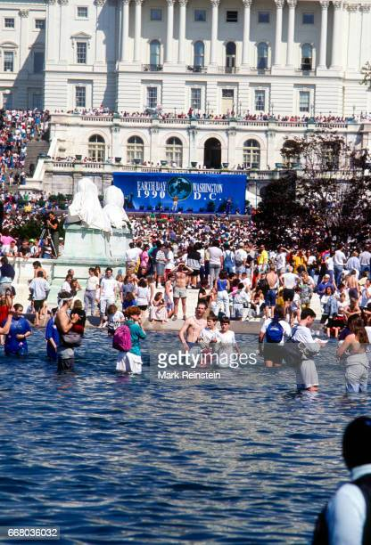 View of the crowd gathered of the US Capitol grounds some in the Capitol Reflecting Pool for an Earth Day rally Washington DC April 22 1990 Visible...