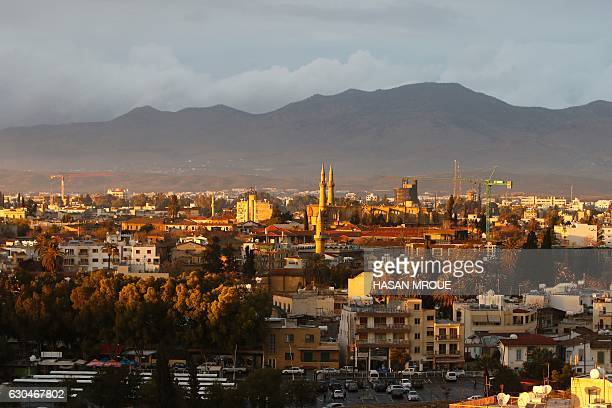 A view of the divided Cypriot capital Nicosia on December 23 2016 with the landmark Suleimiyeh mosque and the Pentadaktylos mountain range in the...