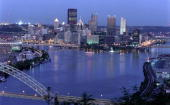 View of the downtown Pittsburgh skyline at dusk showing the Allegheny and Monongahela rivers joining to form the Ohio River Three Rivers Stadium is...