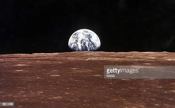 A view of the Earth appears over the Lunar horizon as the Apollo 11 Command Module comes into view of the Moon before Astronatus Neil Armstrong and...