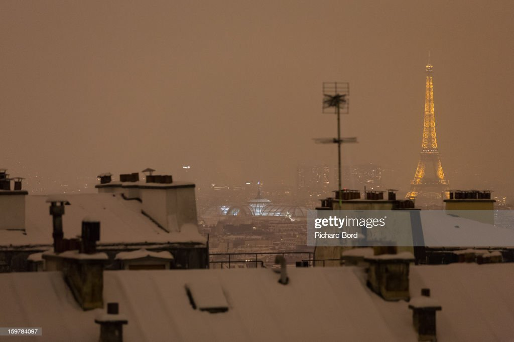 A view of the Eiffel Tower by night from the Sacre Coeur as snow blankets roofs and ground on January 19, 2013, in Paris, France. Heavy snowfall fell throughout Europe and the UK causing travel havoc and white layers of pretty scenery.