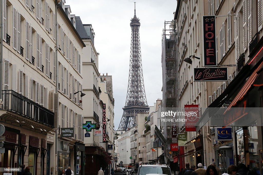 A view of the Eiffel tower rising above buildings in Paris, on May 10, 2013. AFP PHOTO / PIERRE VERDY