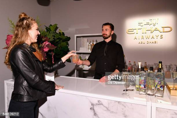 A view of the Etihad Airways bartender with a guest in the Etihad Airways lounge September 2017 New York Fashion Week The Shows Day 6 on September 12...