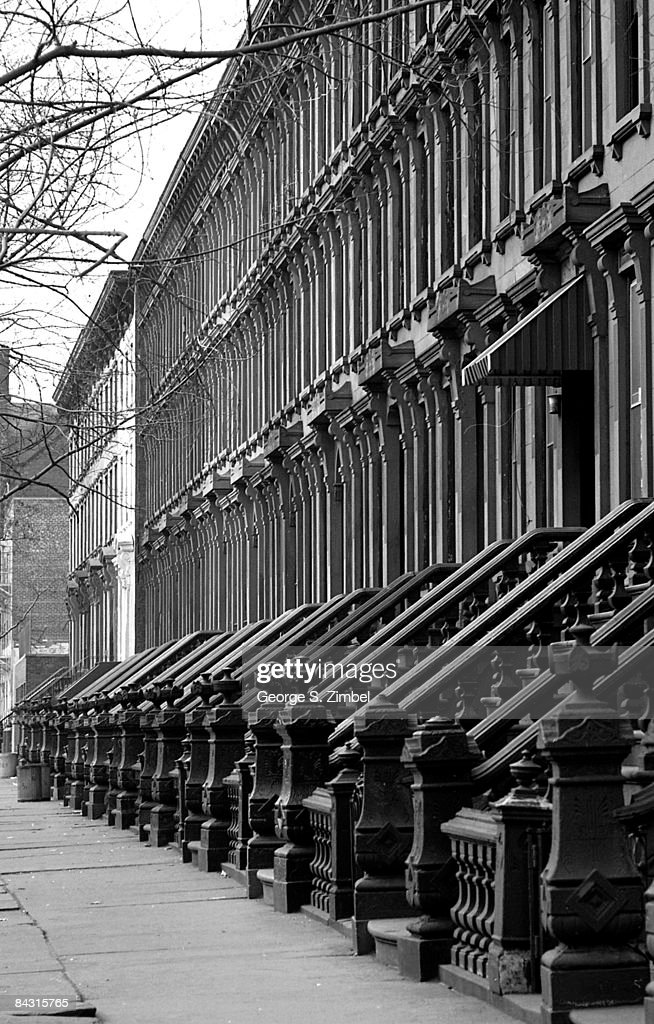 View of the exterior of a row of brownstones on an unidentified street in the Bedford Stuyvesant neighborhood of Brooklyn, 1968. New York.
