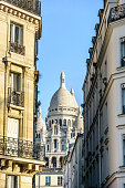 View of the facade and dome of the Basilica of the Sacred Heart in Paris through a narrow street between typical buildings under a clear blue sky.