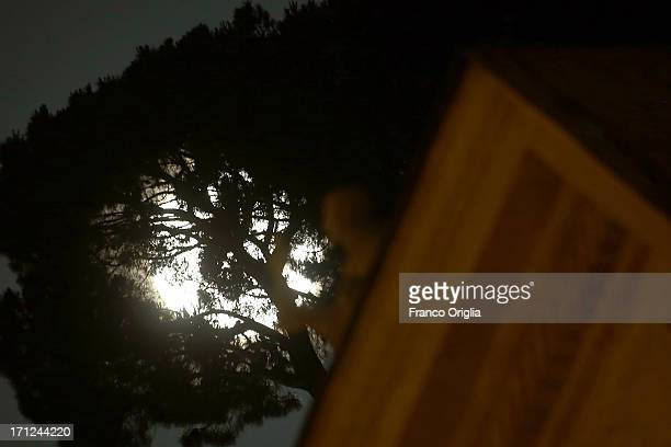 A view of the full moon framed by a pine and the colonnade of St Peter's Square on June 23 2013 in Rome Italy Tonight a pink full moon was expected...