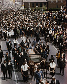 View of the funeral procession of assasinated American minister and civil rights leader Martin Luther King with mourners following the funeral wagon...