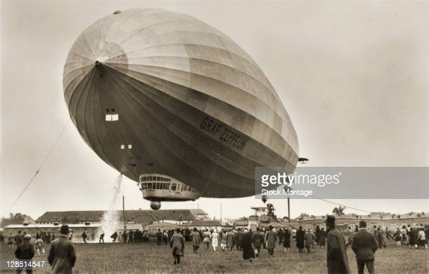 View of the German airship LZ 127 the 'Graf Zeppelin' above an unspecified airfield as it discharges water ballast while a crowd of onlookers watch...