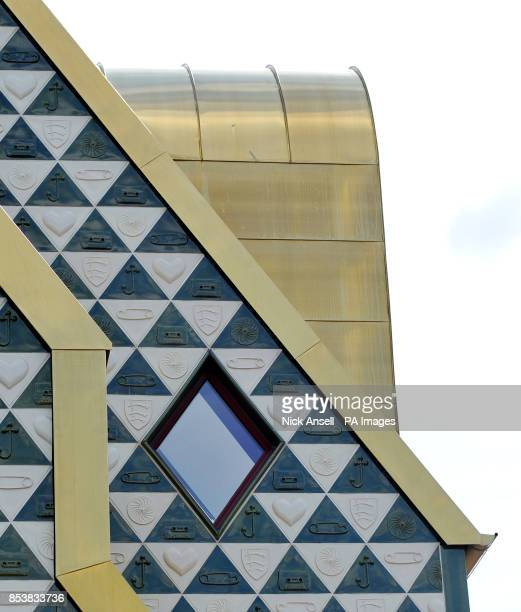 A view of the gold coloured structure and of tiles showing a cassette tape the Essex Coat of Arms a safety pin a heart a wheel pattern and a crossed...