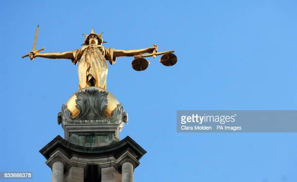 View of the gold statue of the figure of justice holding scales and a sword on top of the Central Criminal Court also referred to as Old Bailey in...