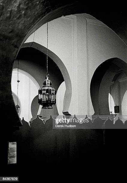 A view of the interior of a mosque and it's lanterns suspended against the double crescent arches