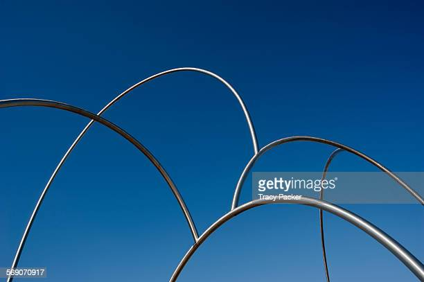 A view of the intersecting tops of 42 foot tall tubular steel arches that mimic waves against a backdrop of clear blue sky These make up the...