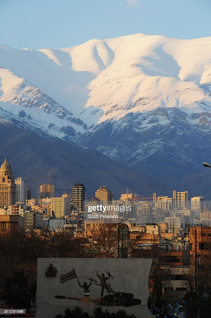A view of the Iranian capital Tehran beneath the Alborz Mountains with a wall sculpture from the recently opened Holy/Sacred Defense Museum a vast...