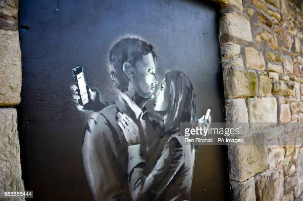 A view of the latest officially confirmed Banksy artwork named Mobile Lovers featuring a man and a woman embraced and looking at their mobile phones...