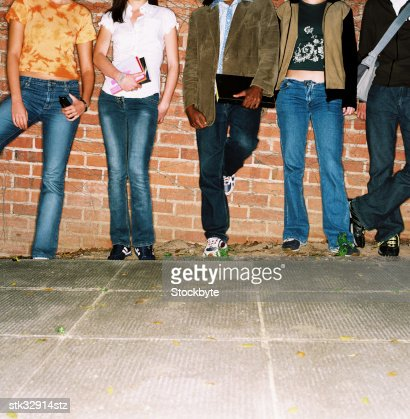 view of the legs of a group of young men and women standing against a wall : Stock Photo