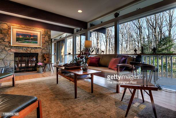 A view of the living room showing the fireplace and wall of windows at the back of this mid century modern home with atrium on January 2012 in...