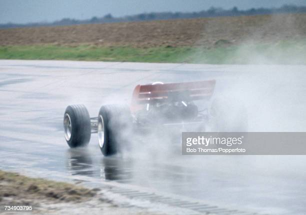 View of the Lotus 72 Formula One racing car being driven in testing on the rain soaked track at Silverstone motor racing circuit near Towcester...