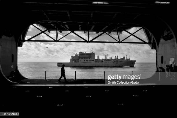 View of the Military Sealift Command dry cargo and ammunition ship USNS Robert E Peary from the hangar bay of multipurpose amphibious assault ship...