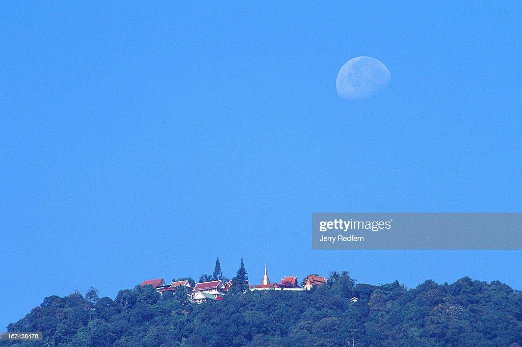 View of the moon setting behind Wat Doi Suthep atop Doi Suthep mountain on the western edge of Chiang Mai..