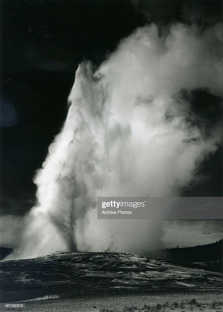 View of the Old Faithful Geyser in Yellowstone National Park as it erupts against a dark sky, Wyoming, 1941.