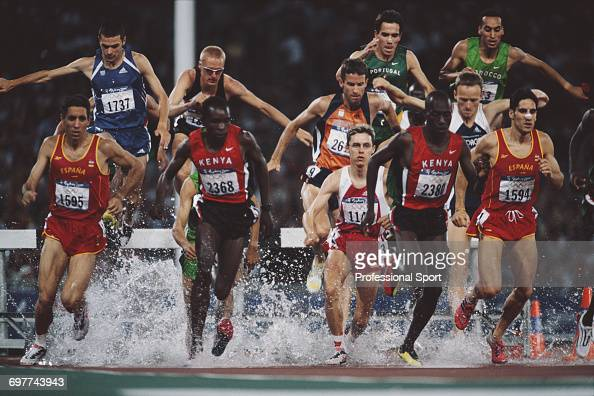 View of the pack crossing the water jump during the final of the Men's 3000 metres steeplechase event at the 2000 Summer Olympics inside Stadium...