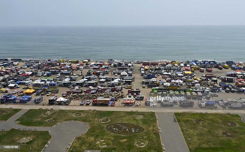 View of the parking lot of the Dakar 2013 Peru-Argentina-Chile competition at a beach in Magdalena, Lima on January 02, 2012. The 2013 Dakar Rally will feature 459 vehicles -- cars, bikes, trucks and quads -- and will cover 8,400km of Peru and Chile, with a stay in Argentina.