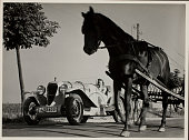 View of the photographer's Opel race car alongside a horsedrawn hay rake on a highway Treptow Germany 1932