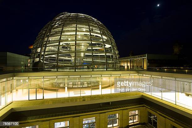 View of the Reichstag dome at night, seen from the other side of a patio.