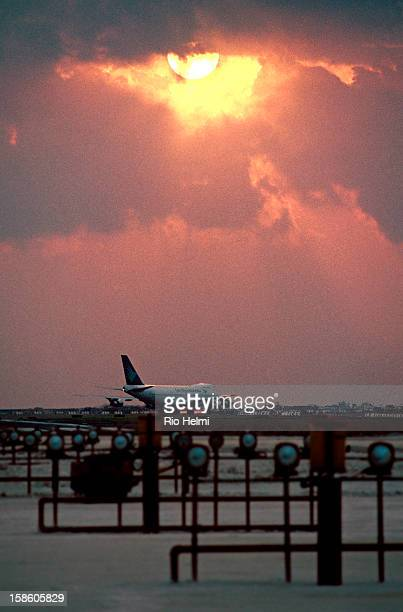 view of the runway of Ngurah Rai airport in Denpasar Bali at sunset with Garuda plane
