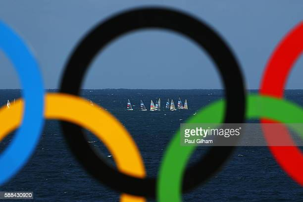 A view of the Sailing through the Olympic Rings during the Men's Preliminary Pool E Match 35 of the beach volleyball on Day 6 of the Rio 2016...