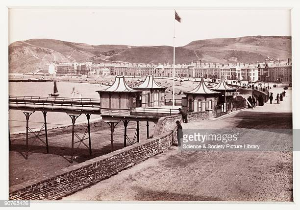 View of the seafront at Aberystwyth West Wales A cigarette kiosk is visibly on the pier which opened in 1865 Photograph published by Francis Bedford...