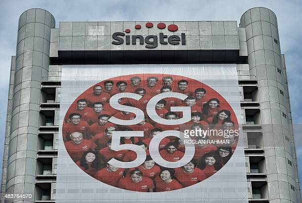 A view of the Singtel logo is seen above a logo for Singapore's 50th anniversary of independence hung from a company building in downtown Raffles...