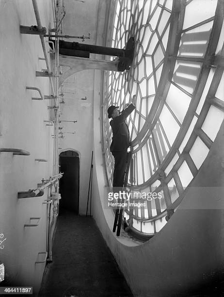 A view of the space behind one of the glass faces of Big Ben in the clock tower at the Palace of Westminster London with a man inspecting repairs The...