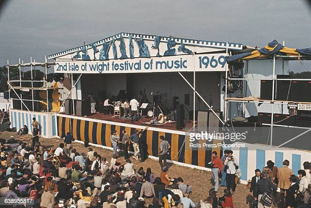 View of the stage at the 1969 Isle of Wight Pop Festival with Indo Jazz Fusions band on stage photographers and audience members sitting on the...