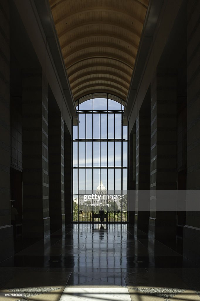 CONTENT] View of the State Capitol of Minnesots from inside the Minnesota History Center in St Paul, MN. A small figure is silhouetted against the very largew window and Capitol building