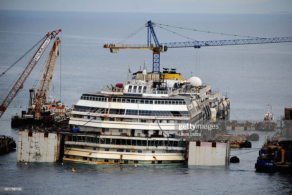 A view of the sunken ship Costa Concordia is seen the day after the last sponson is installed on the port side of the wrecked ship Costa Concordia on July 4, 2014 in Isola del Giglio, Italy. A total of 30 sponsons have been attached to the Costa Concordia to re-floate the ship wreck around July 10th. The wreckage will be removed by the end of July 2014 and will be toed to the port of Genoa for dismantling.