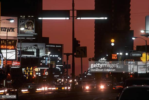 A view of the Sunset Strip looking west with billboard for David Bowie 'Young Americans' and the nightclubs Filthy McNasty's and the Whisky a Go Go...