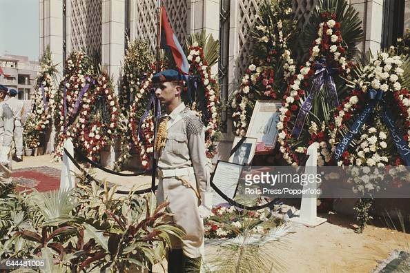 View of the tomb of President Gamal Abdel Nasser of Egypt with large wreaths of flowers and palm fronds surrounding the grave site guarded by...