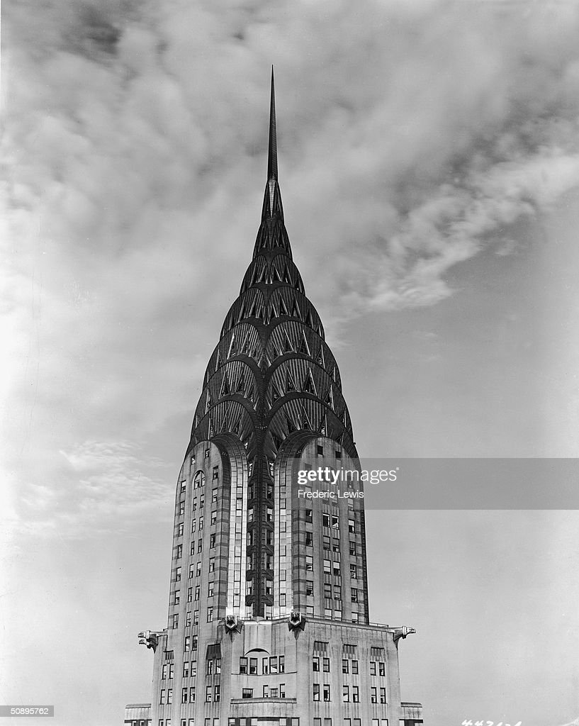 View of the top of the Chrysler Building, clad in steel, arched, spired and with decorative metal eagles, mid 20th Century.
