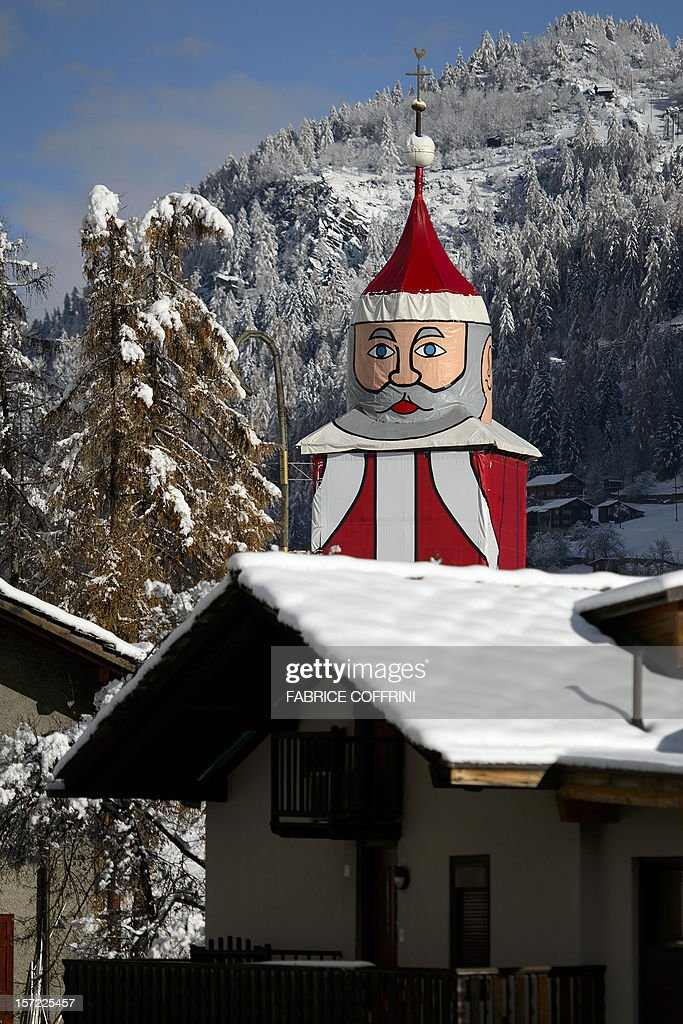 A view of the world's biggest Santa Claus decoration in the mountain village of Saint Niklaus ('Santa Claus' in German), near Zermatt, Western Switzerland, on November 30, 2012. In order to honour the village patron, every year, at the end of November, the 350-year-old, 36.5-metrers high clocktower of the church is transformed into the world's biggest Santa Claus.