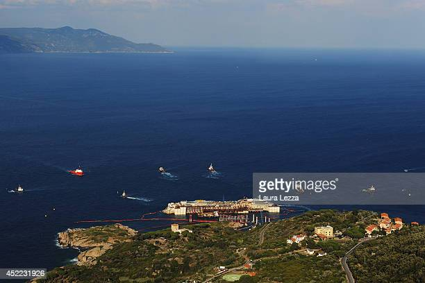 A view of the wrecked ship Costa Concordia and the tugs is seen after the first stage of refloating operations on July 16 2014 in Isola del Giglio...
