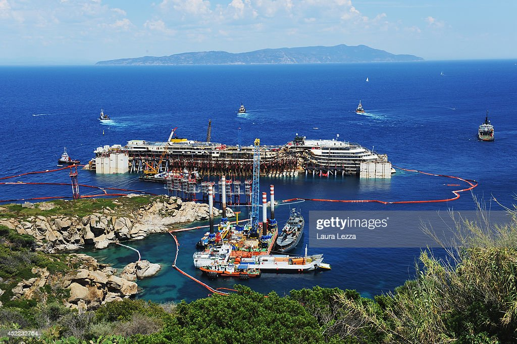 A view of the wrecked ship Costa Concordia and the tugs is seen after the first stage of refloating operations on July 16, 2014 in Isola del Giglio, Italy. The first day of the operation the wreck has been partially refloated by 2 metres from the platfoms that support it and moved approximately 30 metres to the east. The Concordia today has emerged of about 3 meters on average, about 2 meters in the bow area and 4 at the stern.The wreck has been kept in position by tugs and moored by anchors aft, with steel cables. The refloating operation is expected to take up to a week before being towed to the port of Genoa for dismantling.