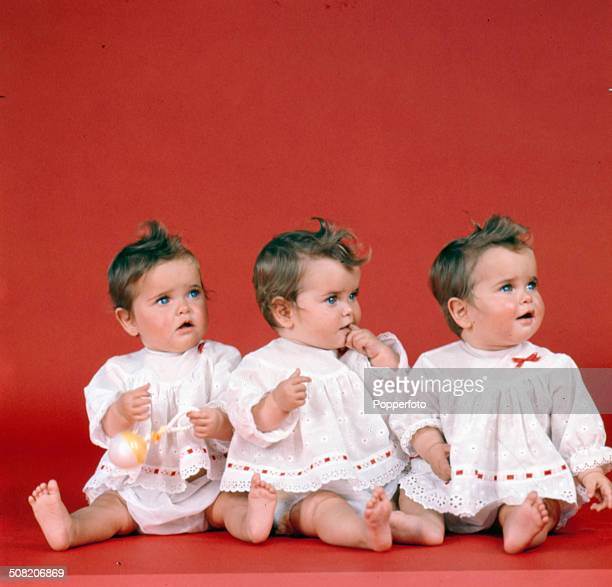 View of three babies wearing identical white dresses in a studio in 1965