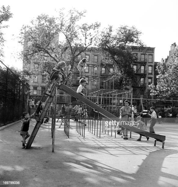 View of three children enjoying a slide in a playground while their mother watches New York New York 1948