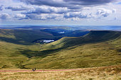 A view of three lakes in the Brecon Beacons National Park in South Wales. A large undulating landscape shot with strong shadows and a very distinct cloud formation. There is a small group of hill walk