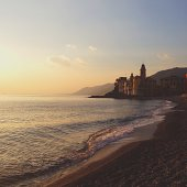 View of town by beach at sunset, Camogli, Italy