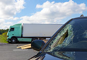 View of truck in an accident with car, cloudy sky