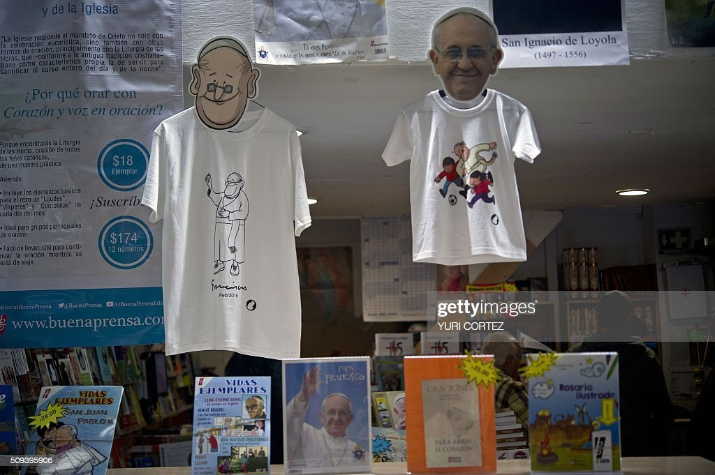 View of t-shirts and masks displaying of Pope Francis for sale at a store in Mexico City on February 10, 2016. Pope Francis will visit four Mexican states from next February 12 to 17. AFP PHOTO / YURI CORTEZ / AFP / YURI CORTEZ